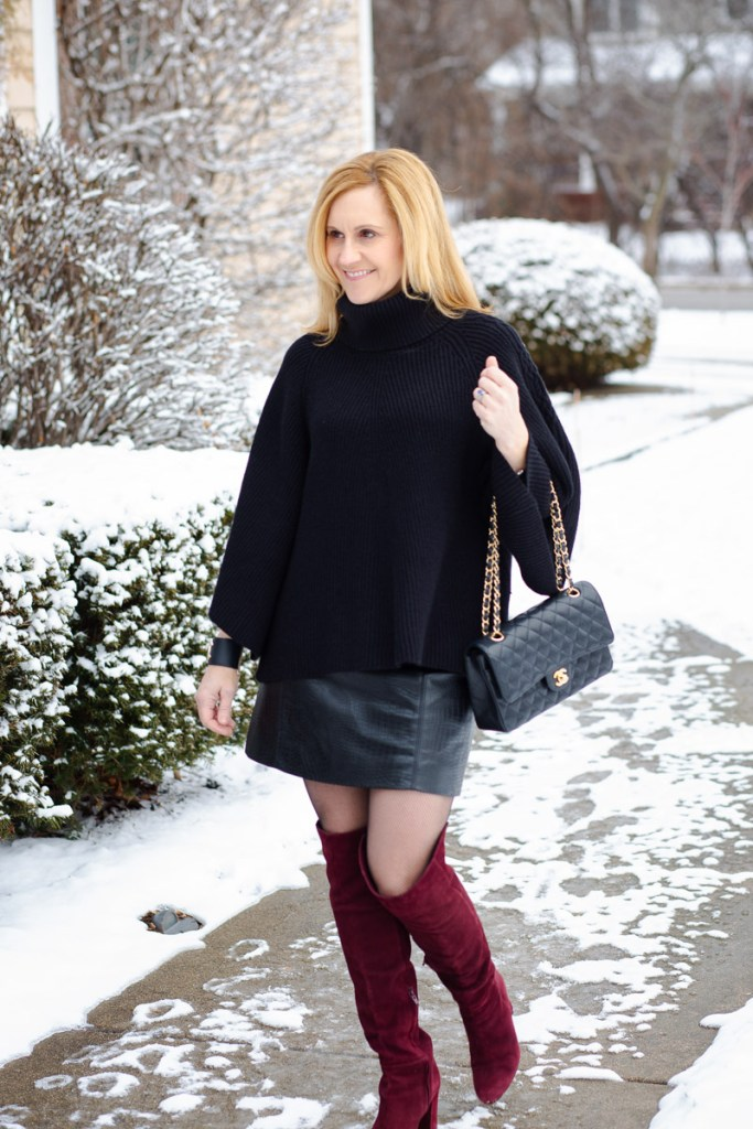 Wearing a poncho sweater with a faux leather mini skirt and otk boots.