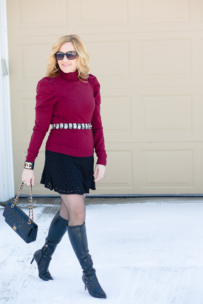 A chic winter look which features a turtleneck layered over a black dress.