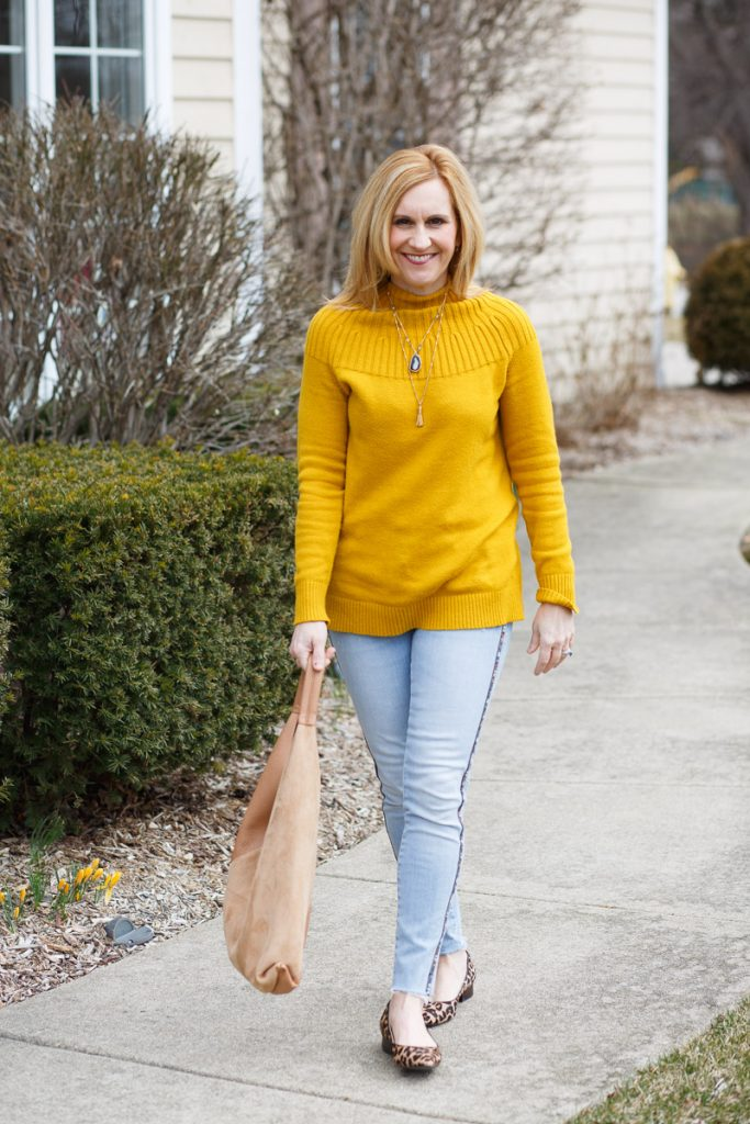 A casual chic spring look featuring a yellow sweater, light denim skinny jeans, and leopard flats