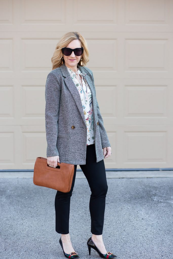 Wearing a double breasted blazer over a floral tank with skinny black pants and pumps.