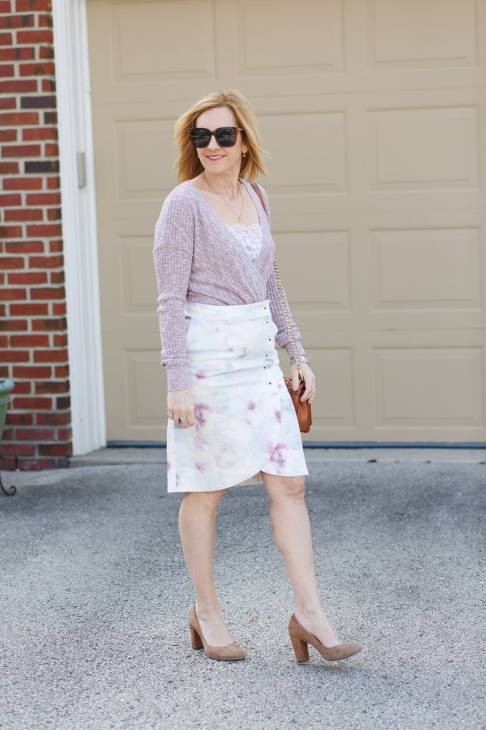 A chic workwear look featuring a pink sweater and tie-dyed skirt.