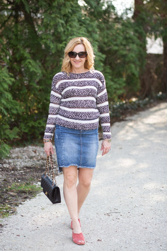 Pairing a casual striped sweater with a denim pencil skirt.