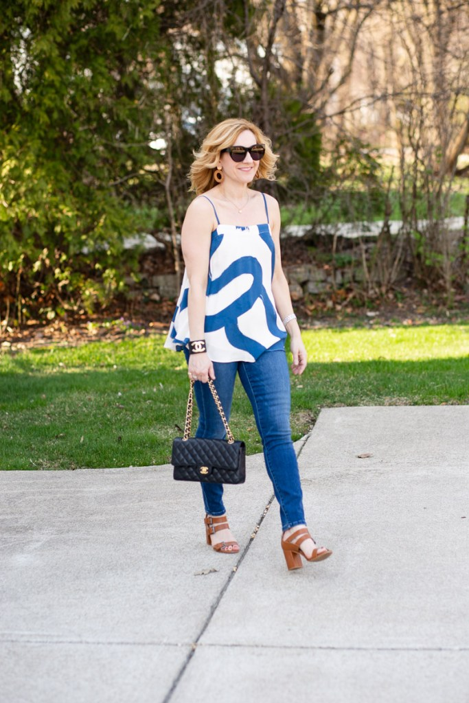 Styling a graphic print swing top with skinny jeans and sandals.