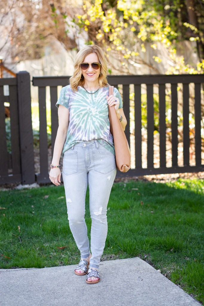 A fun tie dyed tee paired with light grey distressed skinny jeans.