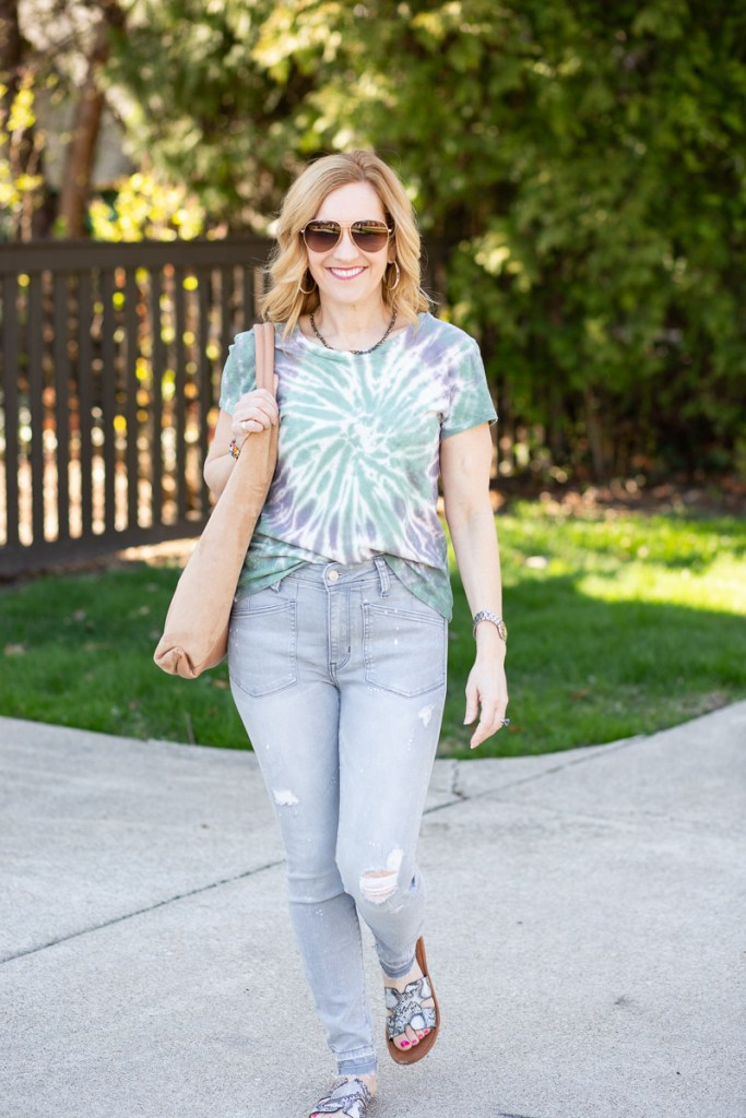 A casual weekend look featuring a tie dye printed tee and light grey skinny jeans.
