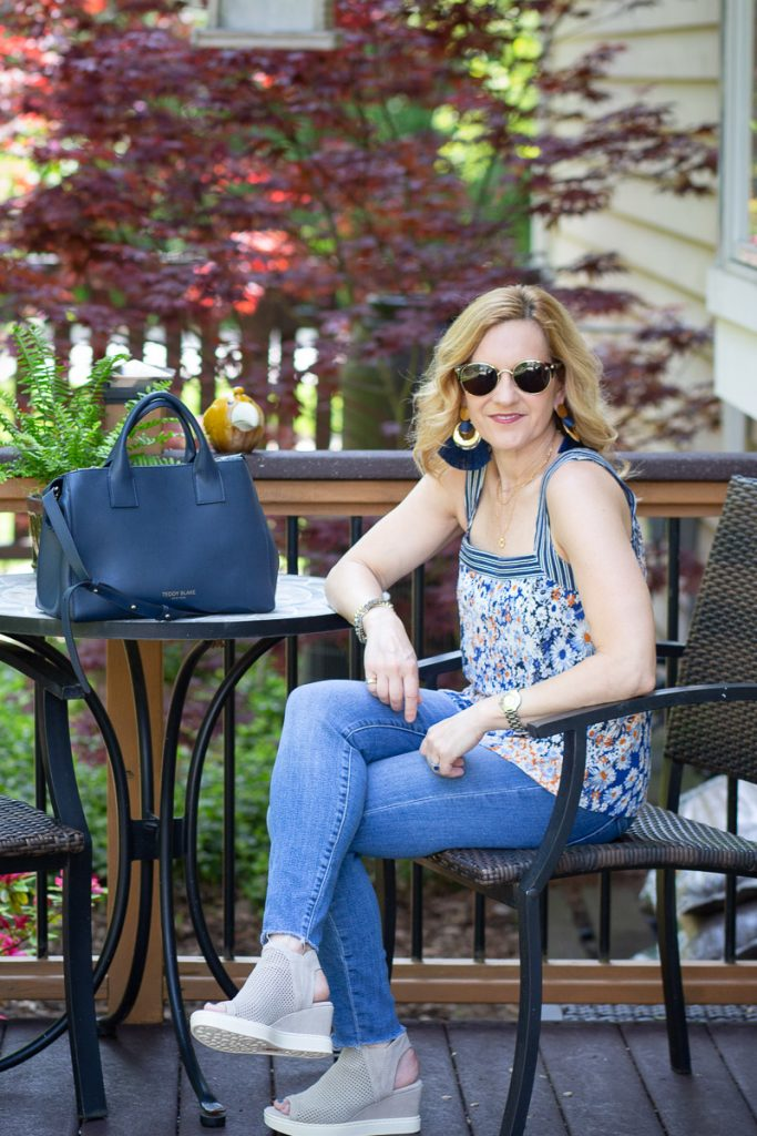 Styling a blue floral square neck tank with skinny jeans and wedges.