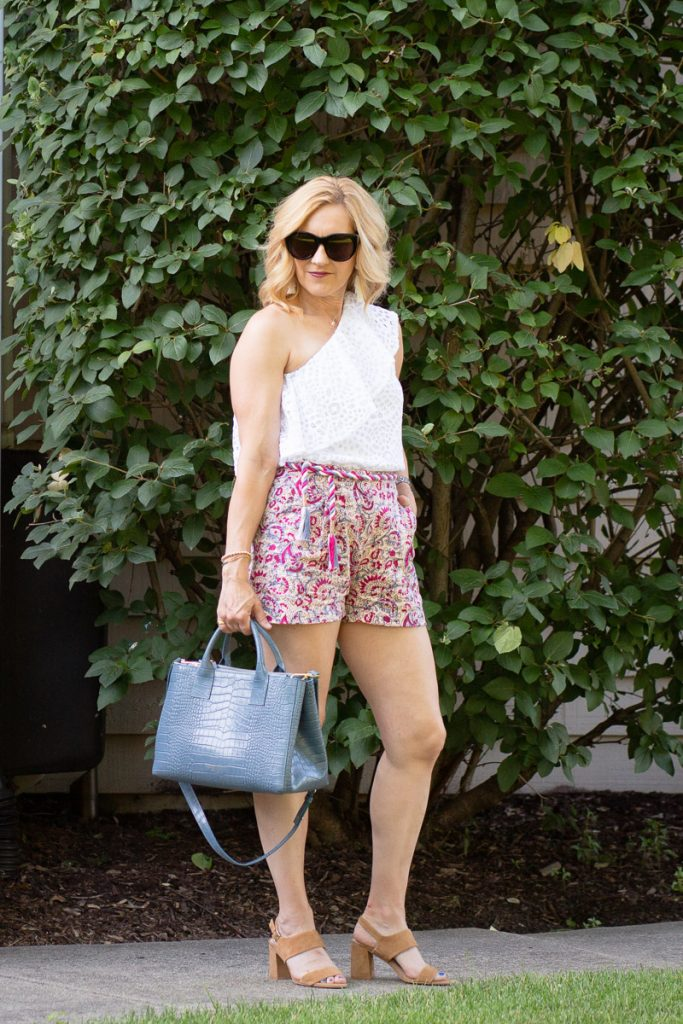 A summer chic look featuring a white one shoulder top, linen shorts, and faux blue croc satchel by Teddy Blake.