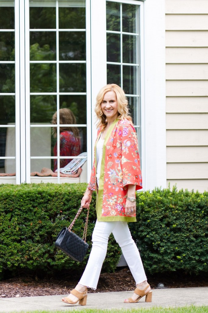 Pairing a coral floral-printed duster with white jeans and sandals.
