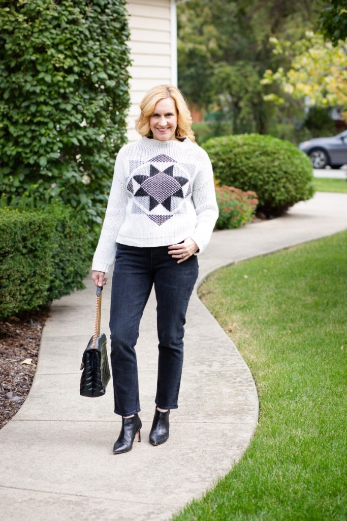 Pairing a cozy white sweater with cropped jeans which are both rented from Nuuly.