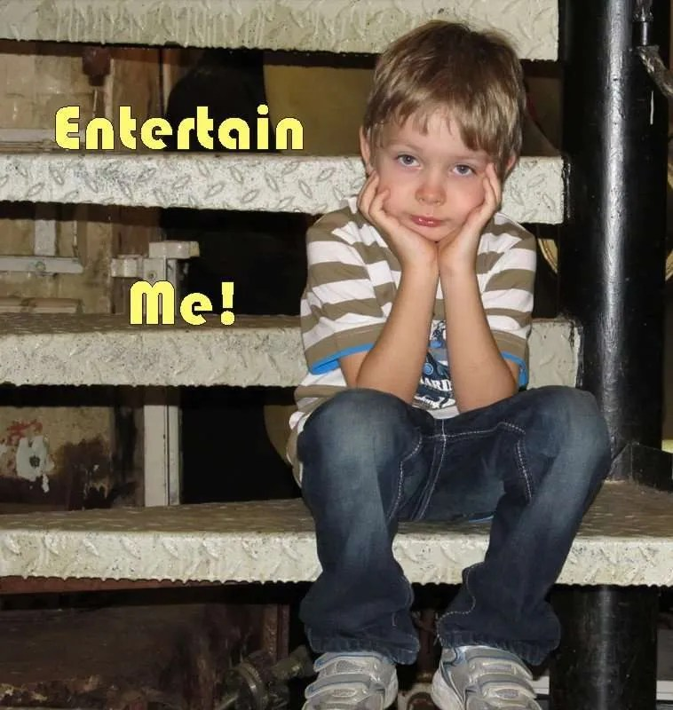 Bored little boy sitting on metal steps with the title Entertain Me.