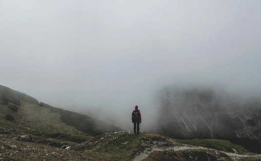 Man standing in front of misty mountains
