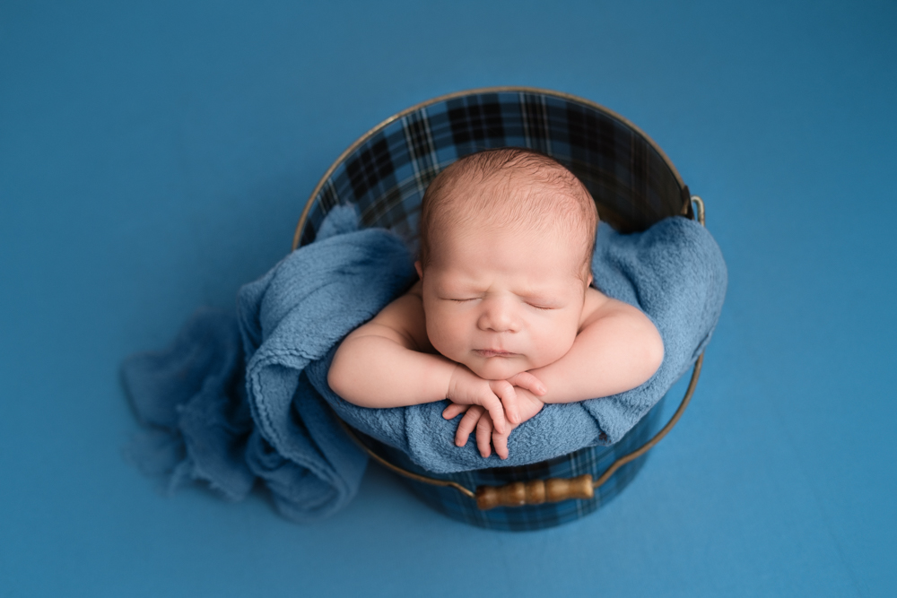 newborn boy in blue bucket