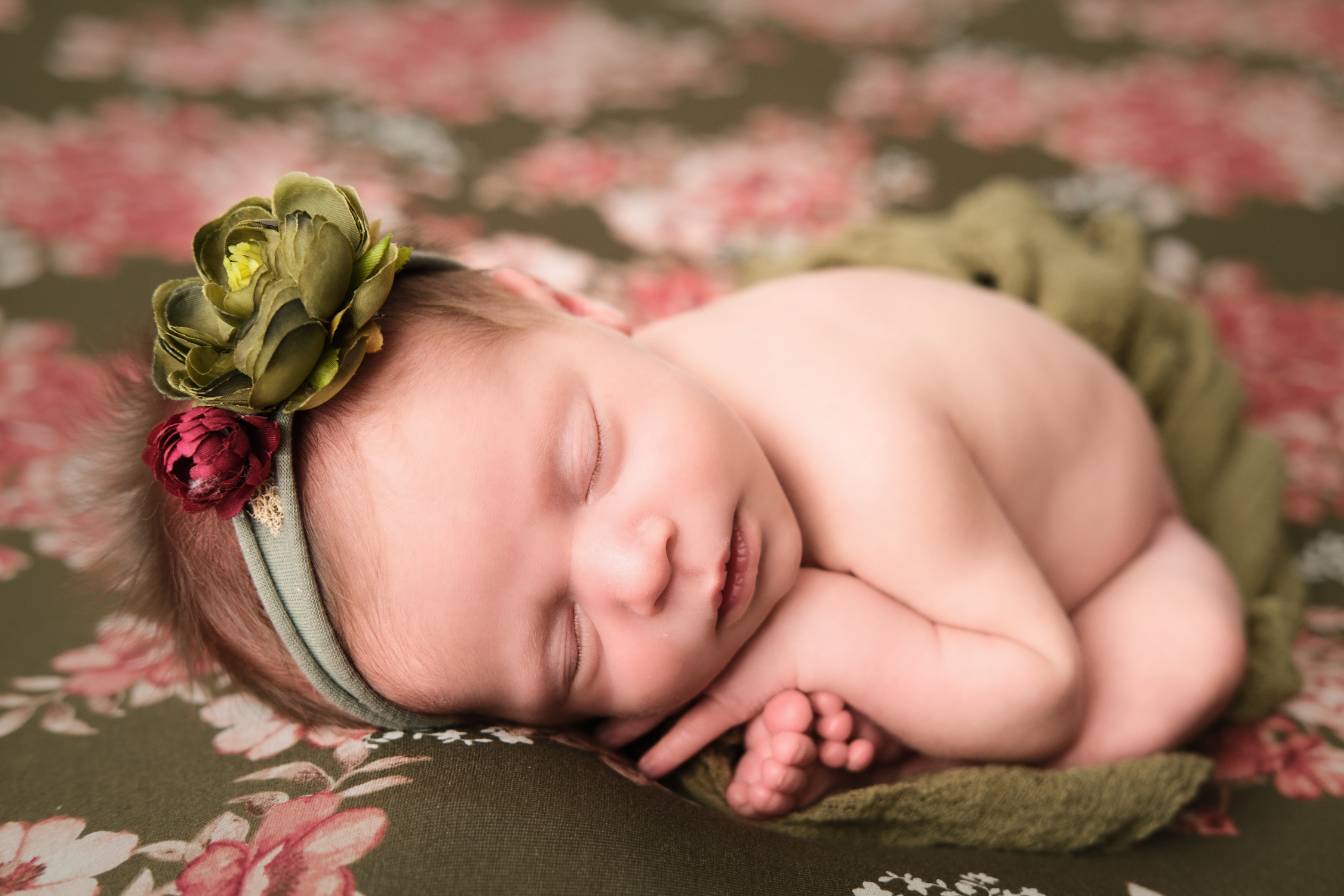baby girl on floral backdrop