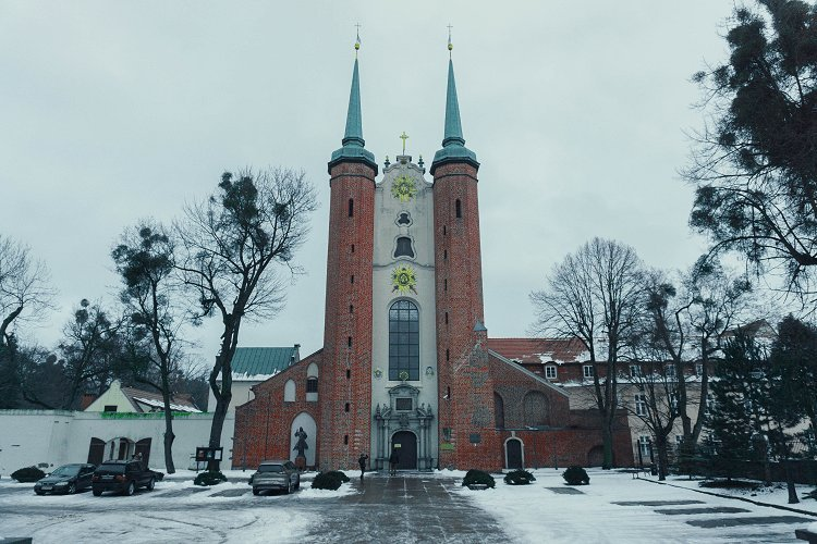 Image of large church building with red and white brick and turquoise spires