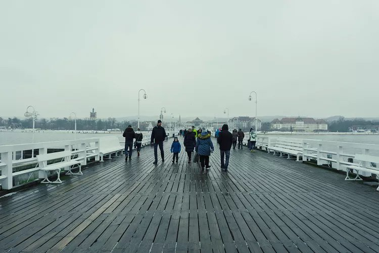 Image of people walking on a wide pier in Sopot in winter