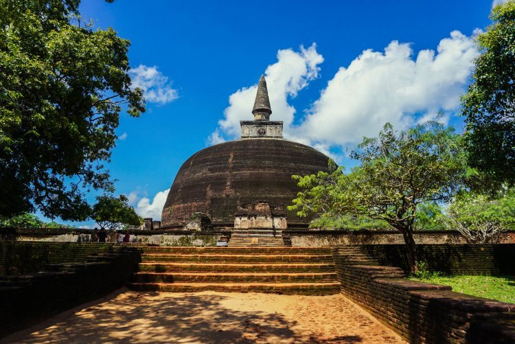 Image of a brown stone circular dome with pointed top ruin structure as part of the ruins of Polonnaruwa in Sri Lanka