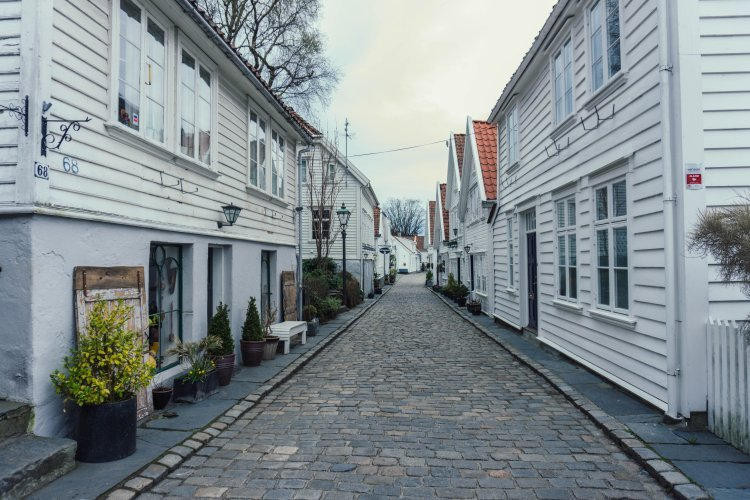 Image of a street in the old town lined with white wooden houses in Stavanger Norway