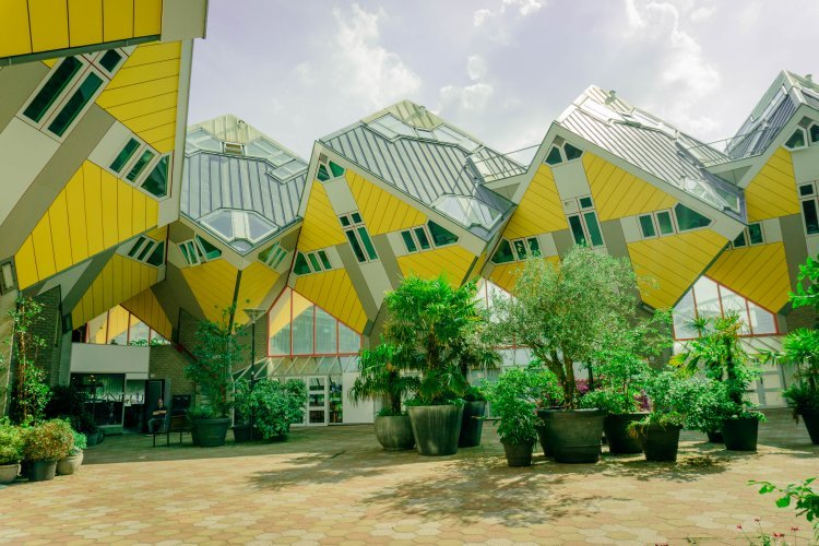 yellow cube houses surrounding an open courtyward with many plants