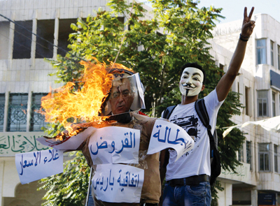A Palestinian protester wearing a Guy Fawkes mask gestures as he stands near a burning effigy of Palestinian Prime Minister Salam Fayyad in Hebron