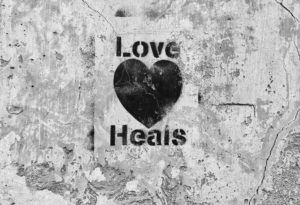 "cement wall with stencil ""love heals"" and a heart"