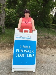 Jill Hetrick stands by the sign for the Erie Highmark Walk