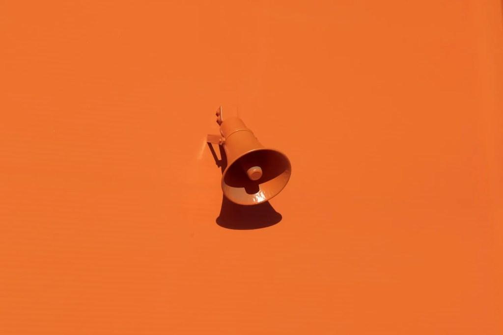 Orange megaphone on orange background.