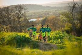 Three mountain bikers walking up a hill in Cheltenham
