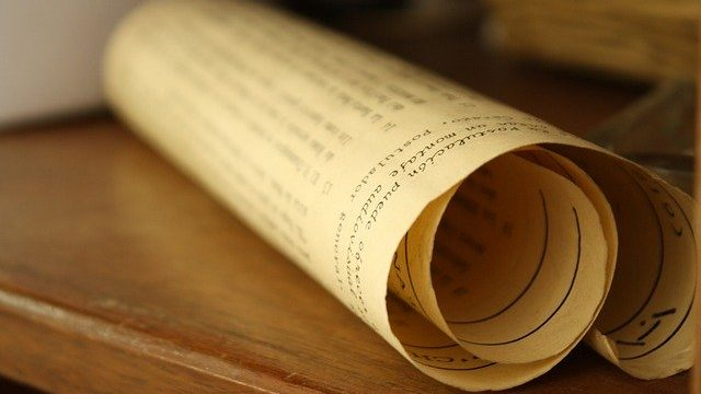 A rolled up paper of text to illustrate the manuscript phase of a book.