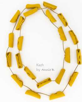 "Coller Kazh de la collection ""Cannelles"" en cuir mat de couleur jaune moutarde."