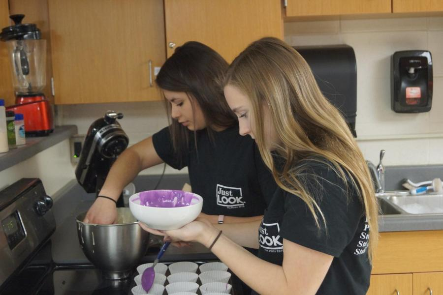 Senior+Taylor+McEachron+and+junior+Morgan+Haworth+pour+batter+into+cupcake+tins.+Their+team+took+first+in+cupcake+wars.