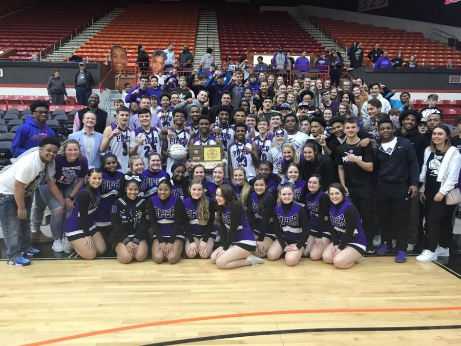 The+boys+basketball+team+poses+with+their+first+place+trophy+with+fans+and+cheerleaders+after+defeating+Augusta.