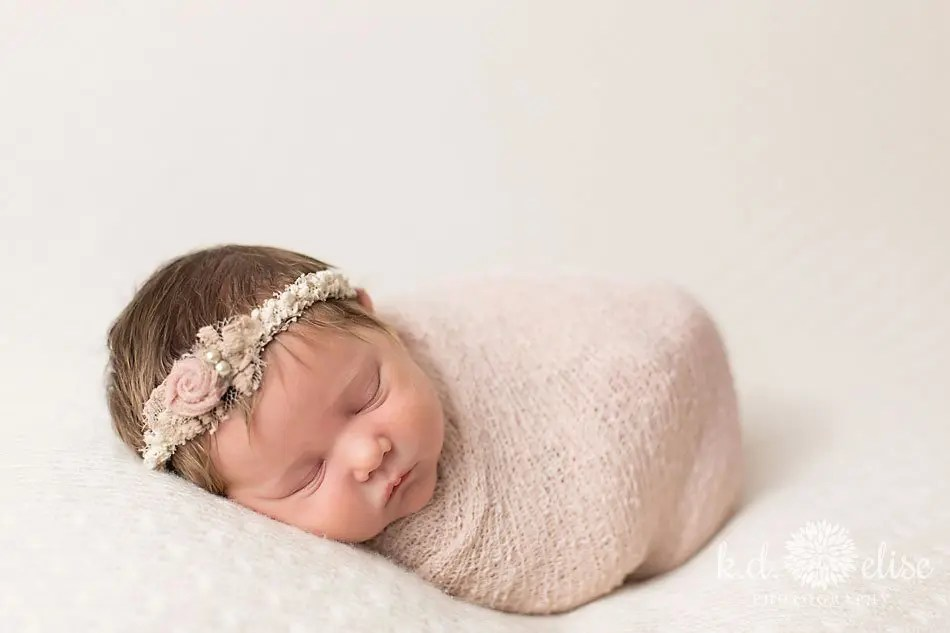 Colorado Springs newborn photographer K.D. Elise Photography- baby girl in pink wrap and pink headband.