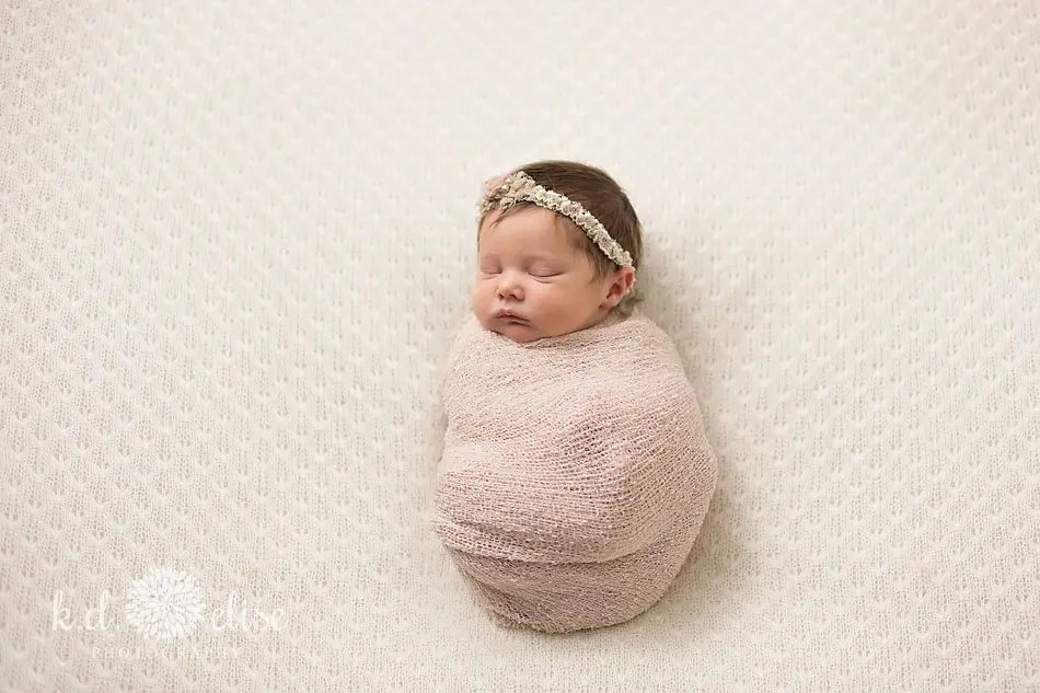 Newborn baby girl in pink wrap by Colorado Springs newborn photographer K.D. Elise Photography