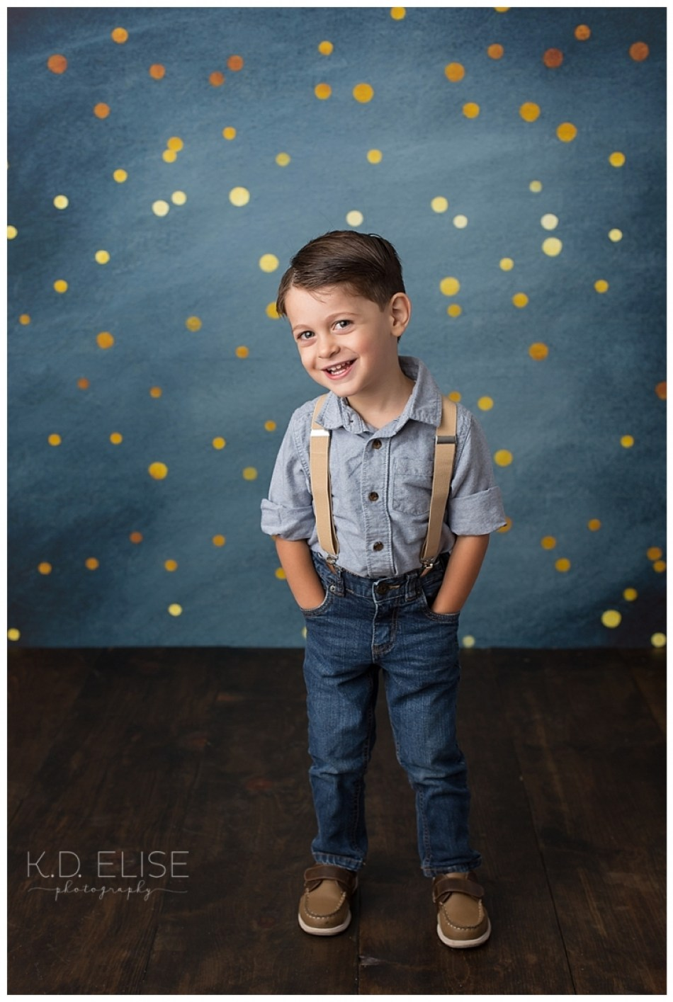 Smiling three year old boy in jeans and suspenders.