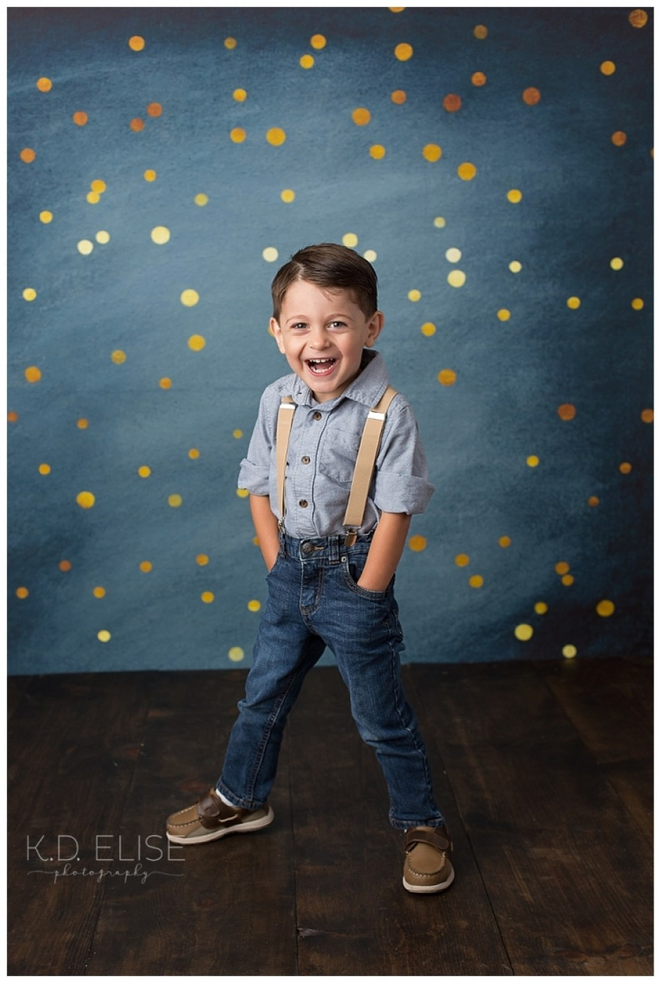 Three year birthday portrait of little boy in blue jeans and blue shirt with suspenders in front of a blue and gold backdrop.
