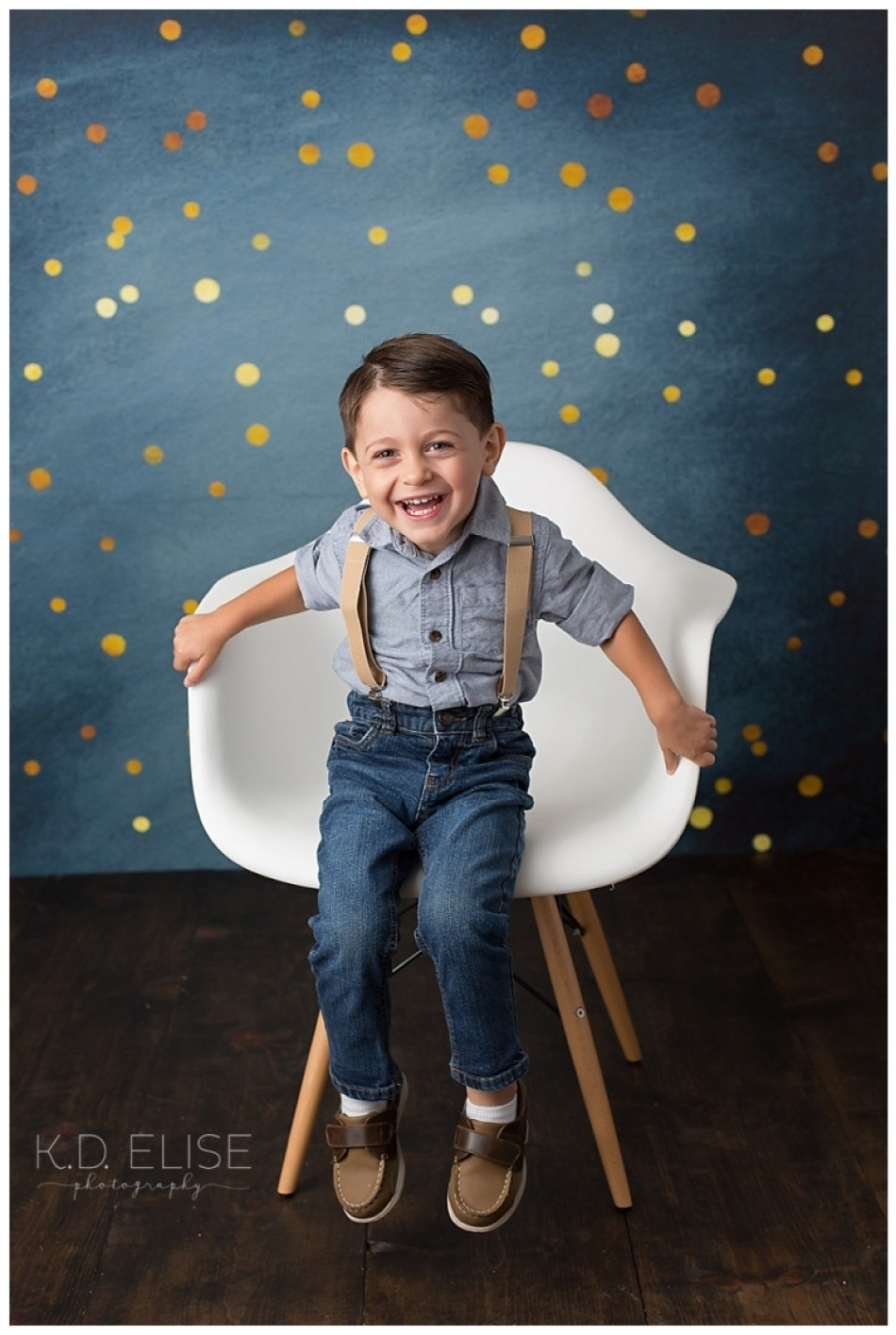 Smiling boy in white chair in front of a blue backdrop.