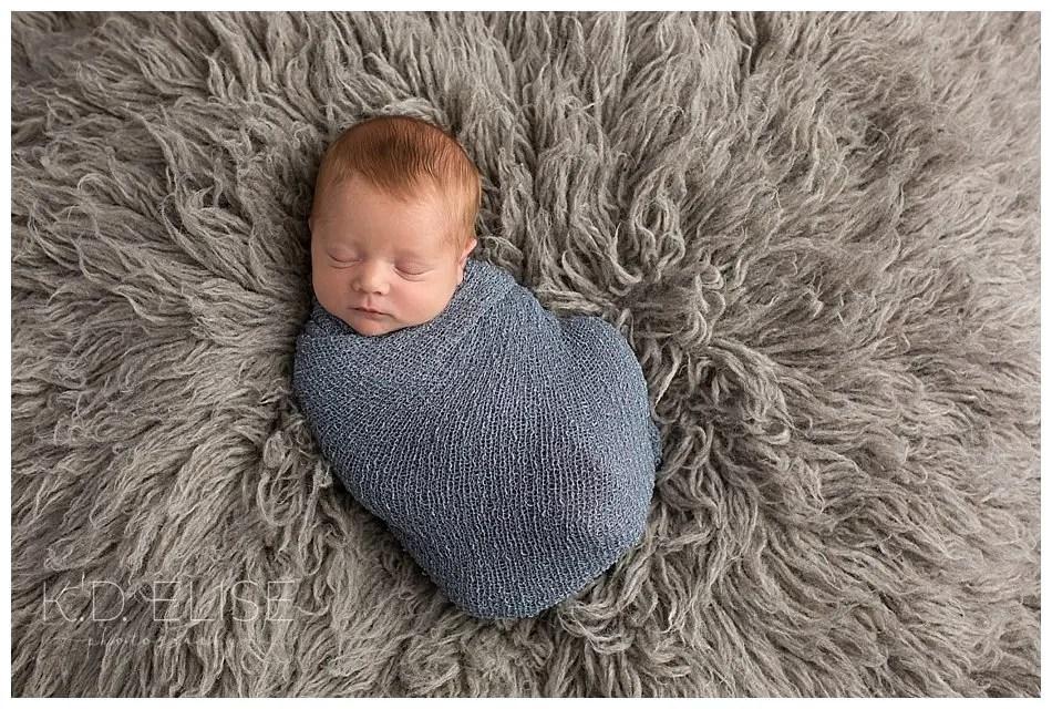 Newborn baby boy in a blue wrap laying on a grey fur.