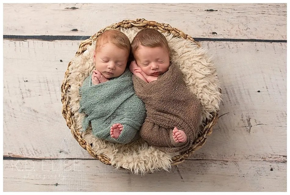 Newborn twin boys wrapped up and placed in a basket.