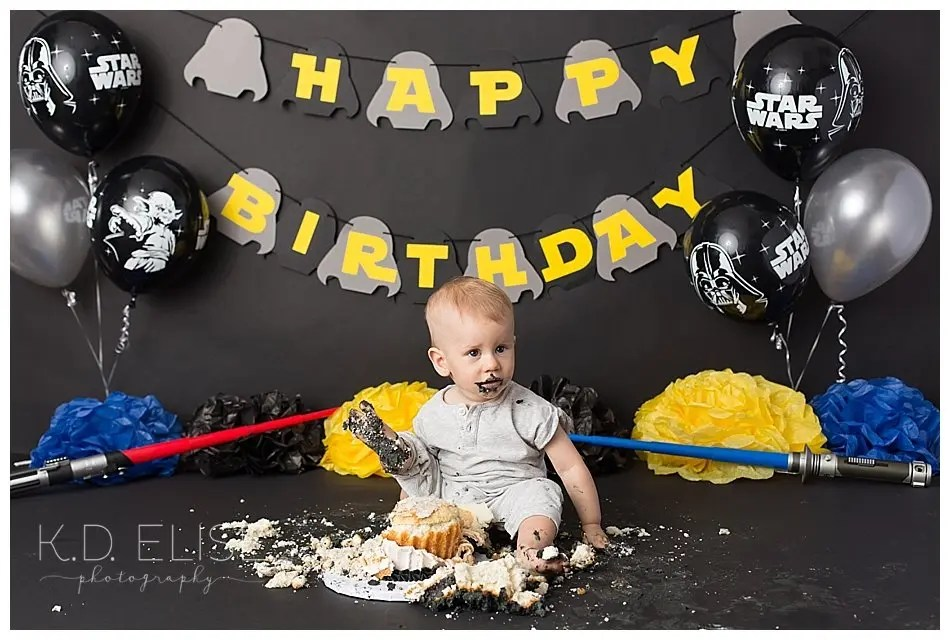 Baby boy eating cake during his Star Wars themed first birthday cake smash.