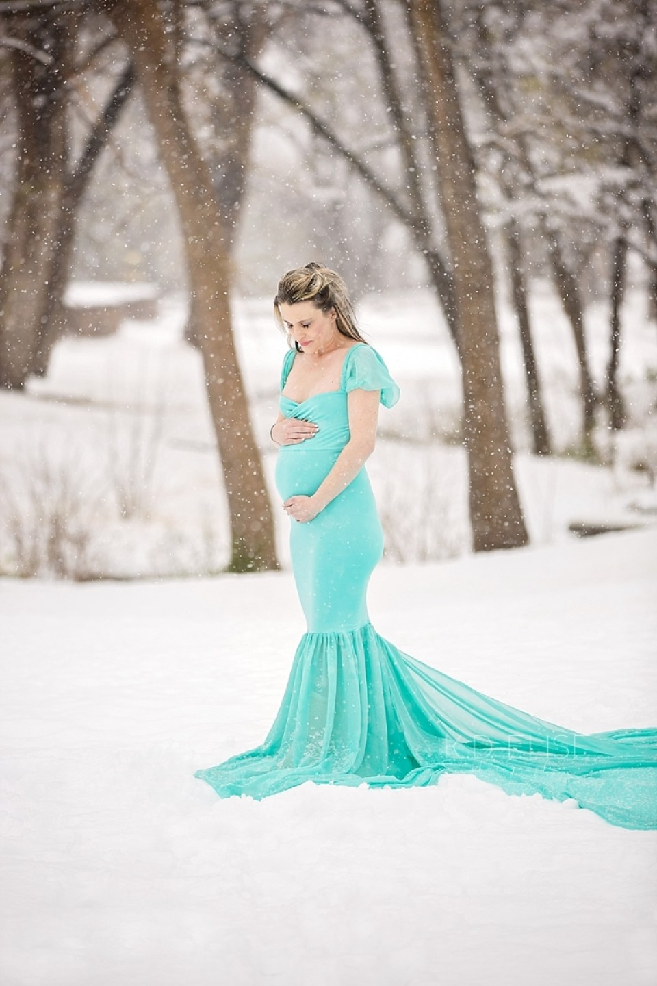 Pregnant mom standing in a snow covered forest during maternity session with Colorado Springs maternity photographer K.D. Elise Photography.