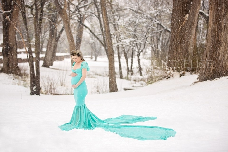 Pregnant mom in tiffany blue gown stands in the middle of a snowy forest during maternity session with Pueblo photographer K.D. Elise Photography.