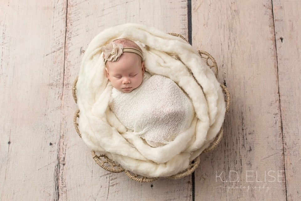 Newborn baby girl wrapped in white, laying a white fluffy fur. Newborn photos by Colorado newborn photographer K.D. Elise Photography.