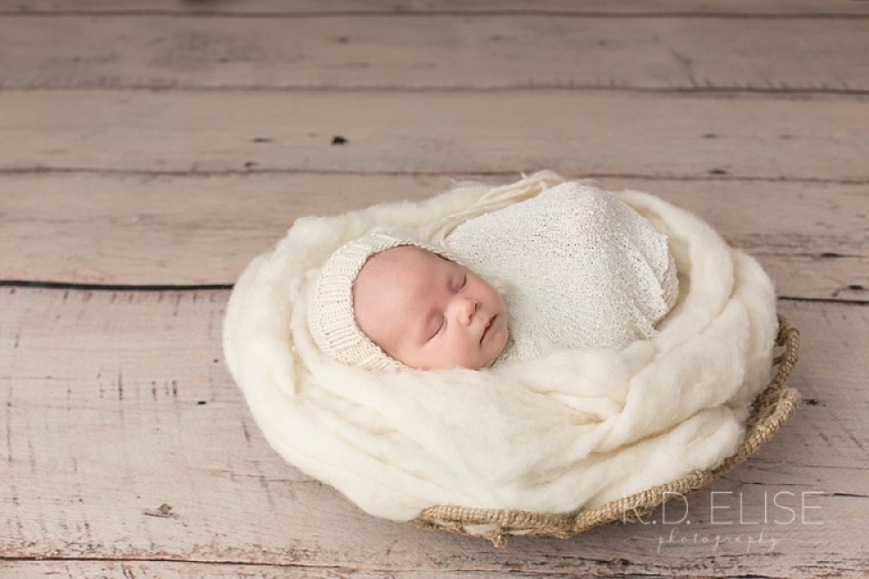 Profile photo of newborn baby girl in a cream bonnet and wrap laying in a basket. Newborn photography by Pueblo photographer K.D. Elise Photography.