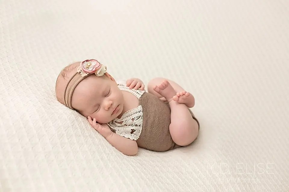 Baby girl in brown and lace outfit curled up on a cream blanket. Newborn photo by Pueblo photographer K.D. Elise Photography.