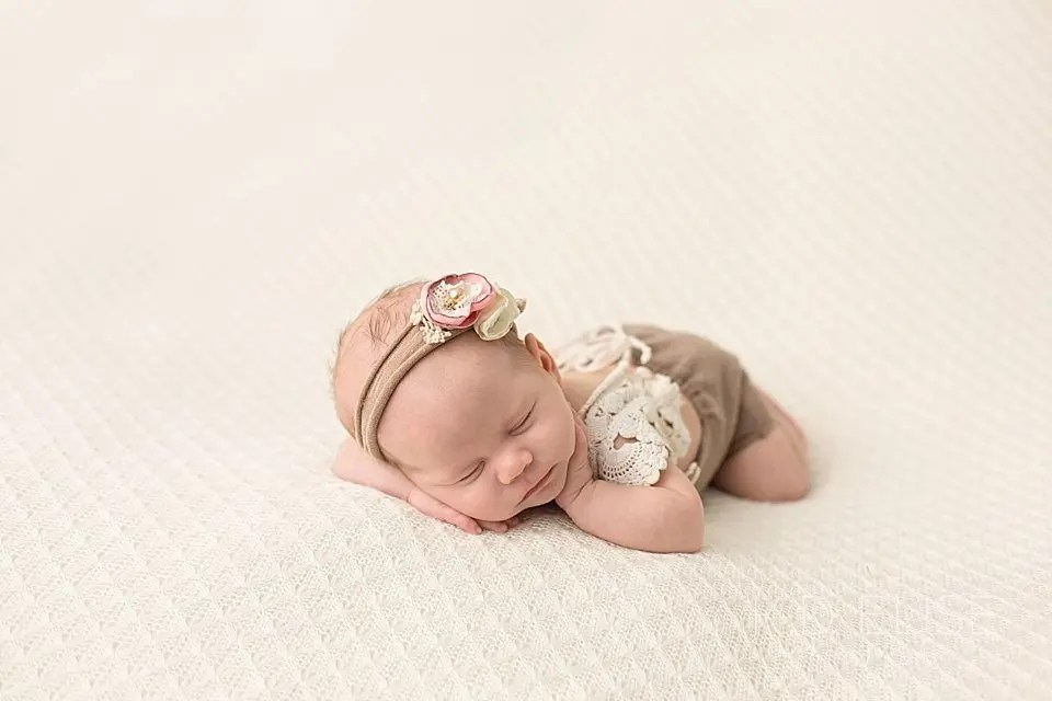 Newborn baby girl in brown outfit with lace trim. Photographed by Pueblo photographer K.D. Elise Photography.