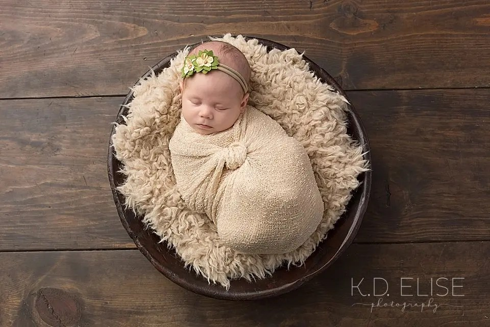 Newborn girl laying a bowl while wrapped in tan fabric. Newborn photography by Pueblo Photographer K.D. Elise Photography.