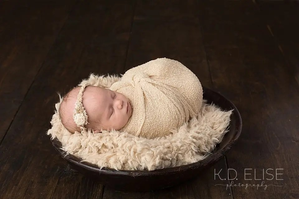 Newborn baby girl in tan wrap, laying a bowl with tan fur. Photo by Pueblo photographer K.D. Elise Photography.