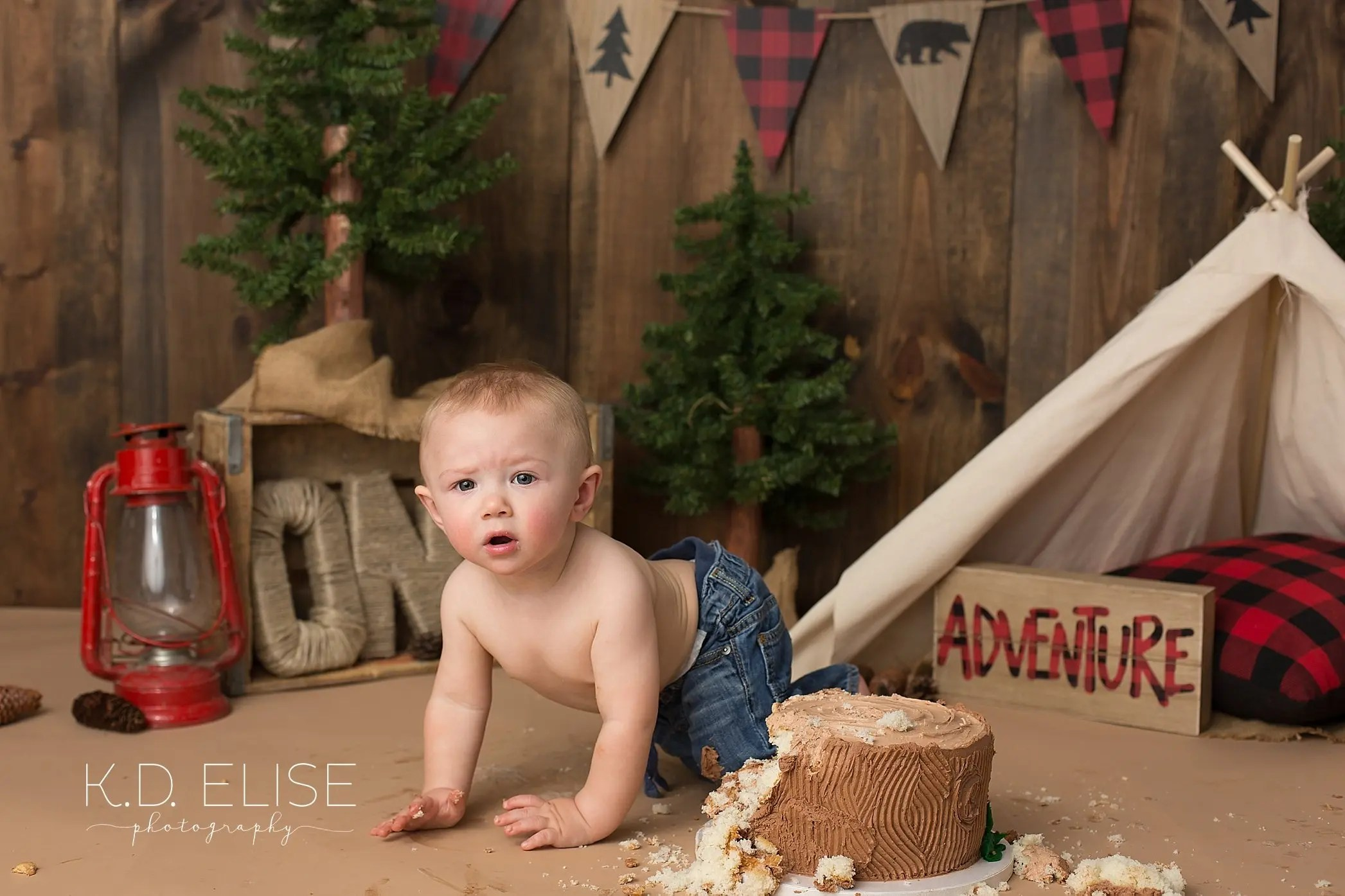 Baby boy crawling away from the cake during lumberjack themed cake smash with Pueblo photographer K.D. Elise Photography