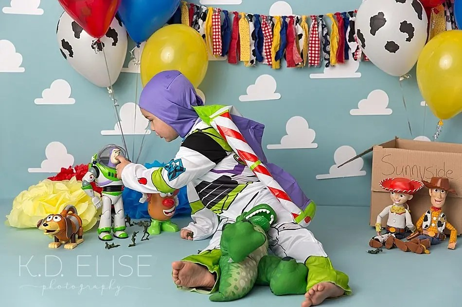 Toy Story themed cake smash photo of little boy in Buzz Lightyear costume.