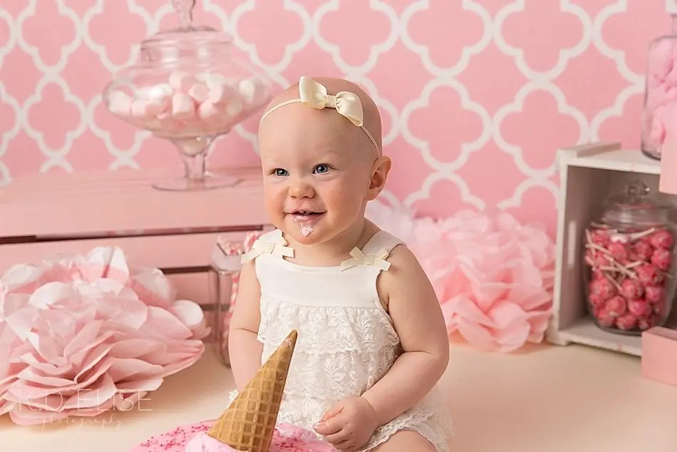 Baby girl sitting in front of an ice cream cone shaped cake during candy themed cake smash with K.D. Elise Photography.